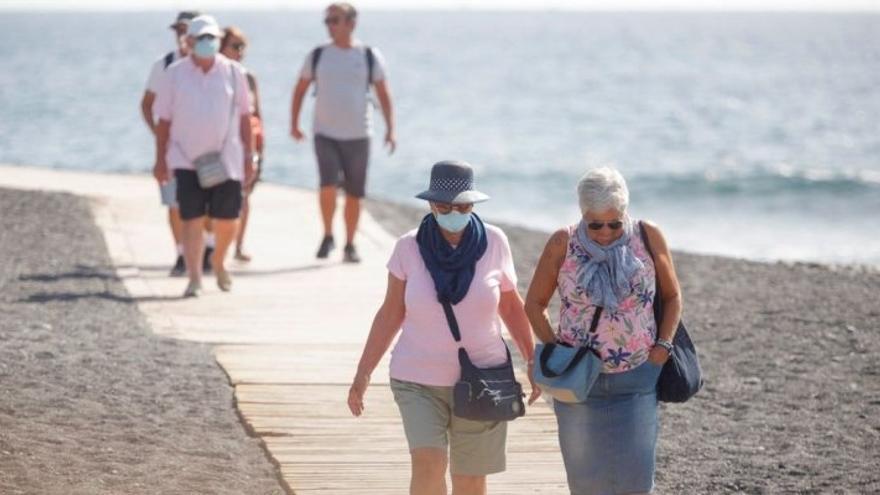 Personas con mascarillas en una playa de Canarias