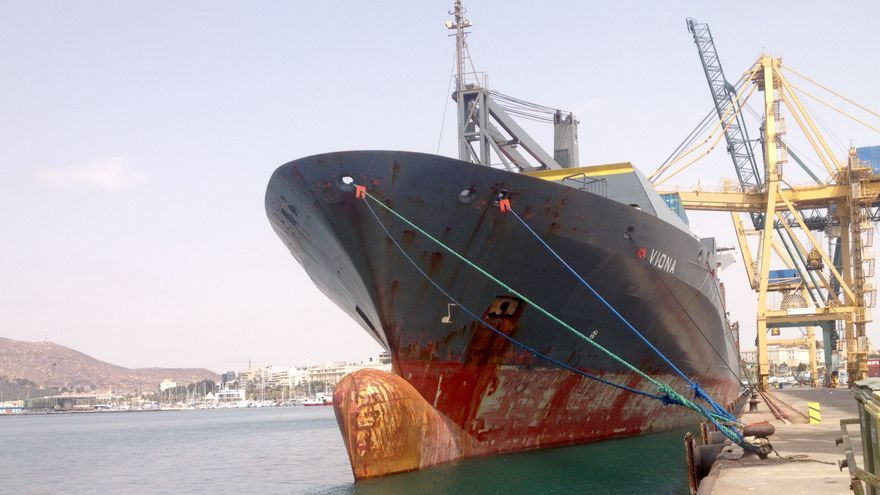 Barco mercante descargando contenedores en el muelle.