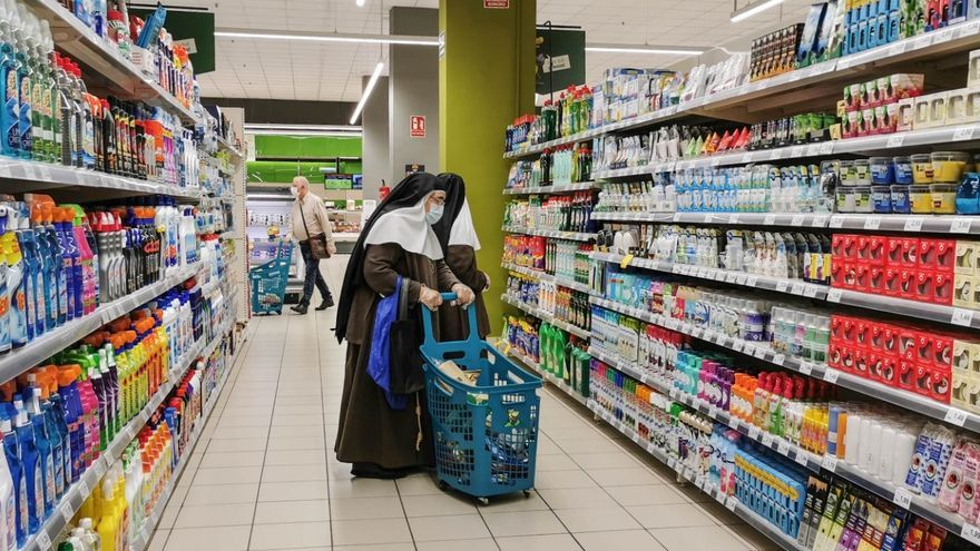 Dos monjas con mascarilla compran en un supermercado.