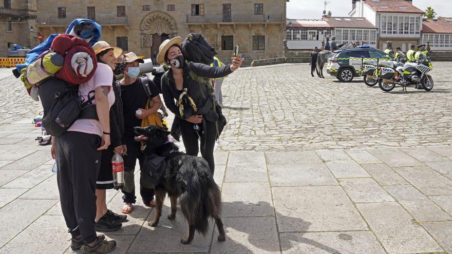 Varios peregrinos se toman una foto, a su llegada a la Catedral de Santiago