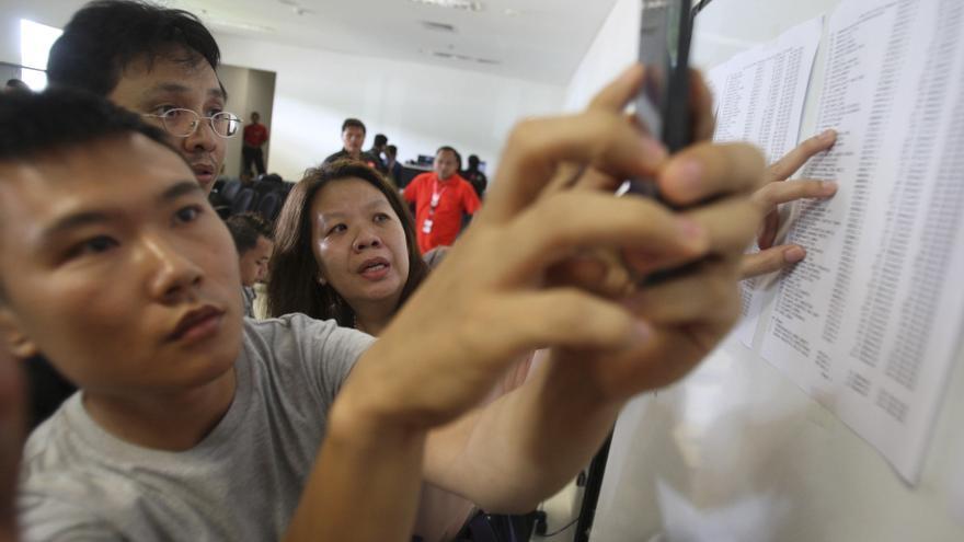 Familiares de los pasajeros del avión de AirAsia desaparecido comprueban las listas del pasaje en el aeropuerto de Surabaya (Indonesia). \ Trasnadi (AP Photo)