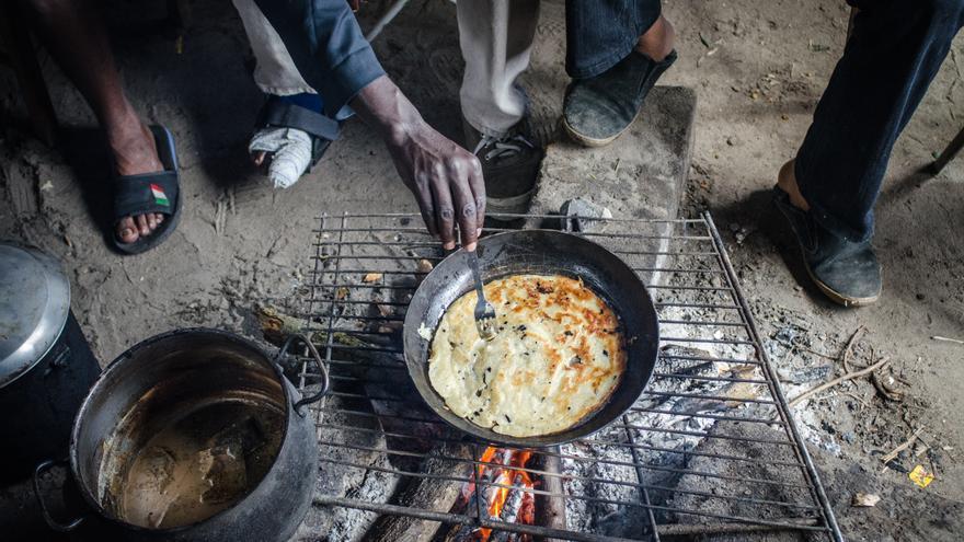 Refugiados sudaneses, algunos visiblemente heridos, cocinan al aire libre en el campamento de La Jungla, en Calais. / Foto: Thom Davies.