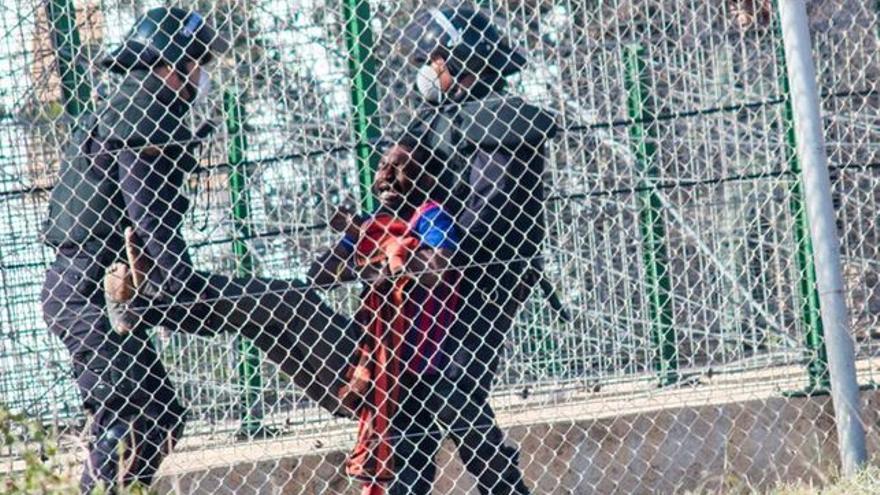 Imagen de archivo de dos agentes que devuelven a un inmigrante a Marruecos tras el intento de salto del 1 de mayo de 2014. / Foto:José Palazón.