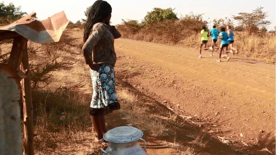 Fotograma del documental en el que se observa como una mujer atiende el paso de un grupo de corredores