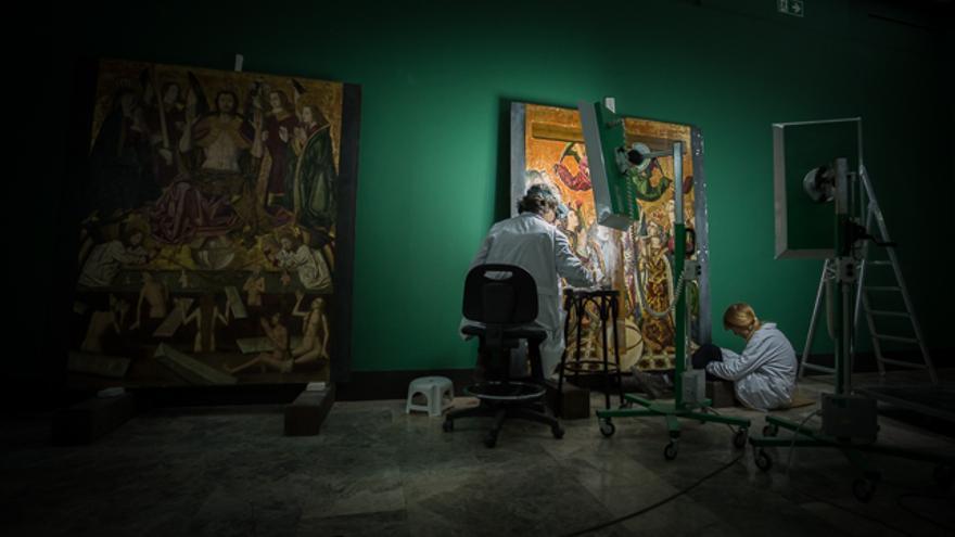 Pilar Camón y Elena Naval trabajan sobre la Adoración de la Cruz del retablo de Blesa, en la sala de gótico del Museo de Zaragoza.