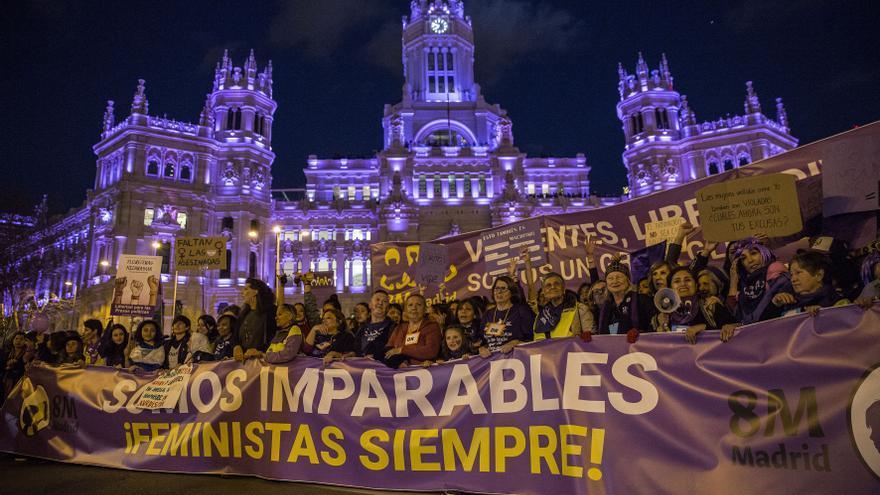 Imparables: el edificio del Ayuntamiento del Madrid, iluminado de violeta, contempla el paso de la cabecera de la manifestación del 8M en 2019