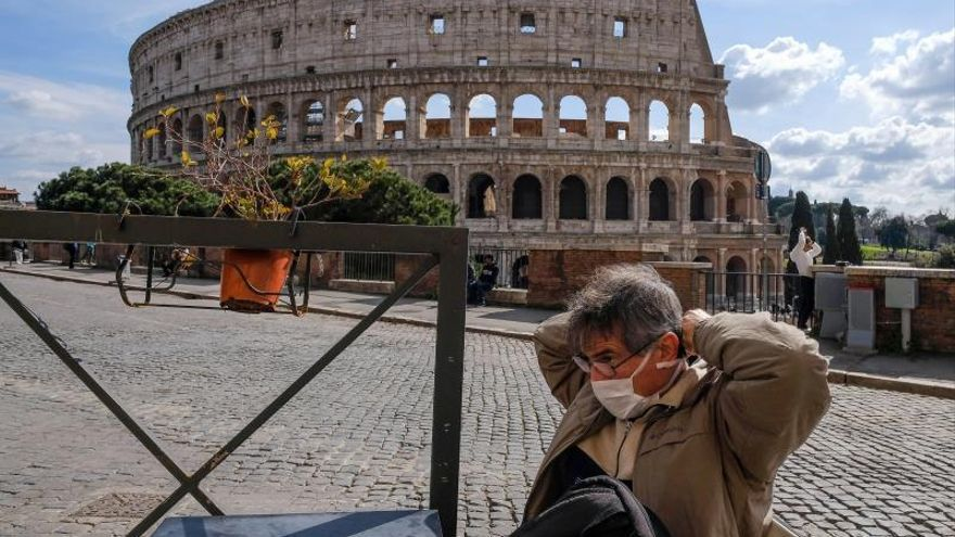 Un vecino se coloca una mascarilla frente al Coliseo, en Roma