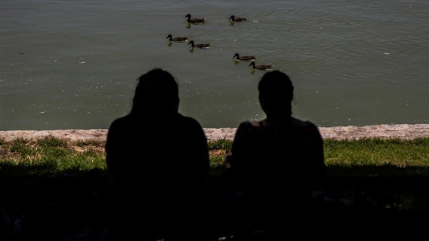 Dos personas toman el sol en el lago de la Casa de Campo en Madrid este martes.