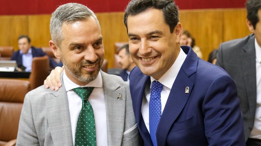 El presidente andaluz, Juan Manuel Moreno, felicita al consejero de Hacienda, Juan Bravo, antes del debate presupuestario.