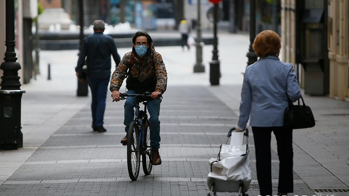 Personas con mascarilla y bicicleta en el centro de Córdoba