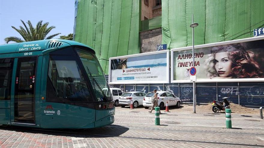 El tranvía pasa junto a unas de las vallas publicitarias que recrean la ciudad de Atenas / Ramón de la Rocha, Efe