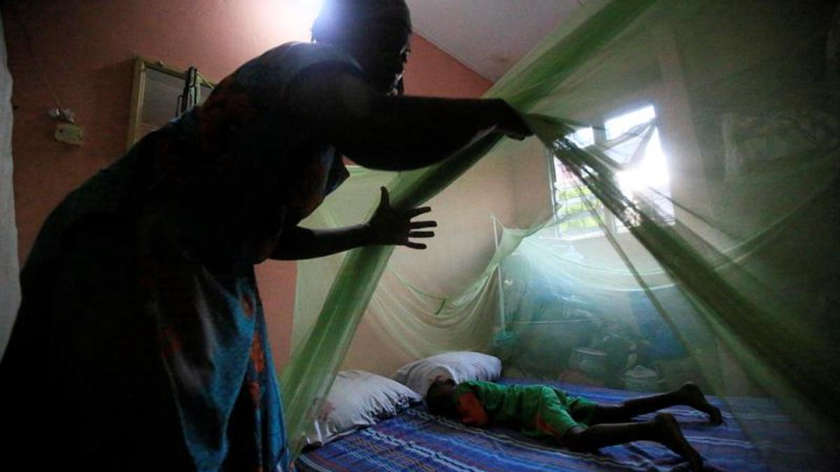 Imagen de archivo. Una mujer cubre a un menor con una mosquitera, herramienta esencial contra la malaria.