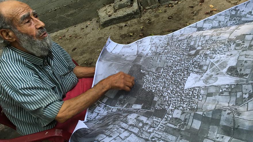 Refugiado palestino de Hamama en un campo de refugiados de la franja de Gaza señalando en un mapa de 1945 dónde estaba su casa antes de ser destruida por los israelíes. | Foto cedida por De-Colonizer.
