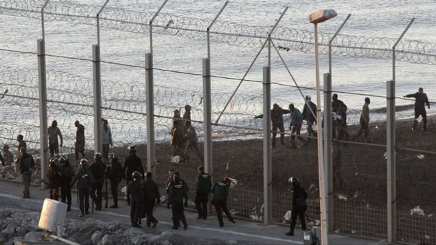 Las fuerzas españolas de seguridad e inmigrantes a ambos lado de la valla de Ceuta, junto al agua. / Efe