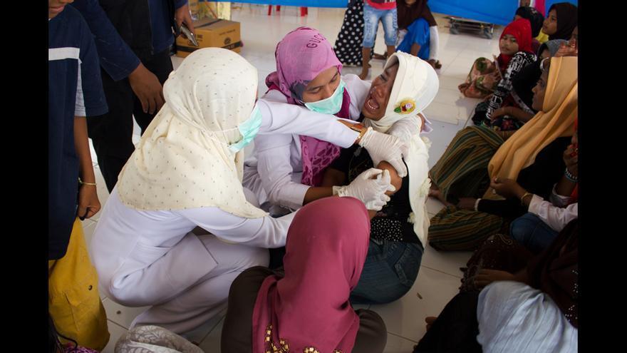 Una mujer rohingya recibe una vacuna contra el tétanos en el campo de Kuala Cangkoi, en Aceh (Indonesia). Presa del pánico, la mujer lloraba desconsoladamente y se zafaba cuando los médicos trataban de ponerle la inyección y varios de ellos tuvieron que calmarla y agarrarla para conseguirlo. Como muchos otros rohingyas, no había visto una jeringuilla en su vida. Muchos de los rohingyas que viven en las zonas rurales de Arakan (Birmania) no han recibido jamás ningún tipo de asistencia sanitaria. © Carlos Sardiña Galache / Yayasan Geutanyoe – A Foundation for Aceh.