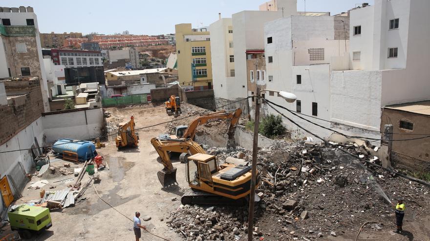 Tractores y obreros trabajan retirando escombros y, al fondo, bajo la casa amarilla, se aprecia el Barranco de La Ballena.