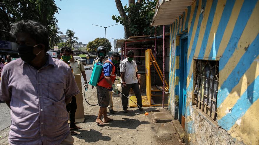 Trabajadores municipales desinfectan un puesto policial en Bombay (India)