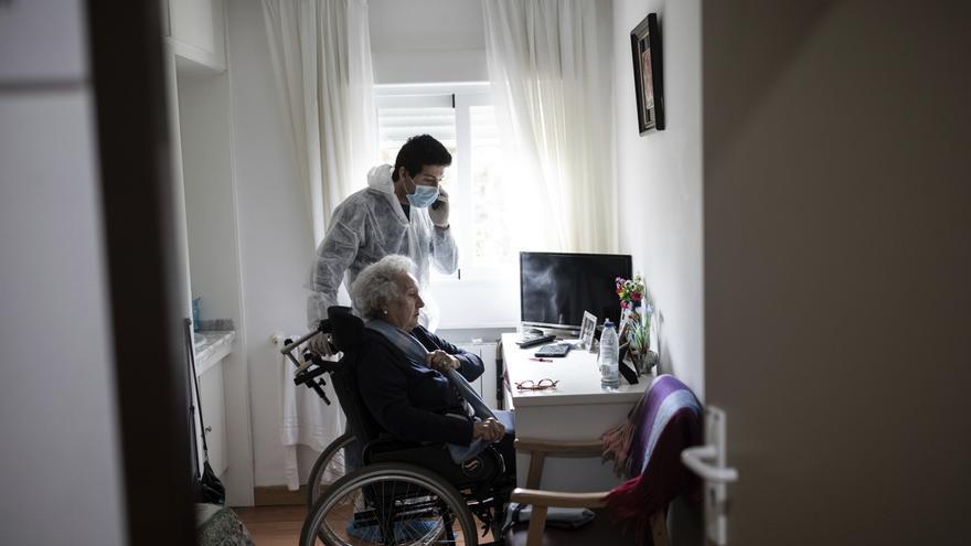 Personal de la residencia para mayores de Pozuelo de Alarcón ayuda a una mujer a comunicarse con sus seres queridos / AP Photo/Bernat Armangue