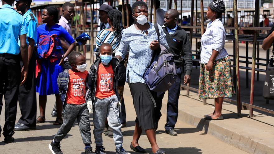Una mujer y sus hijos llevan mascarillas mientras caminan por una calle muy transitada en Harare (Zimbabwe), este 31 de marzo