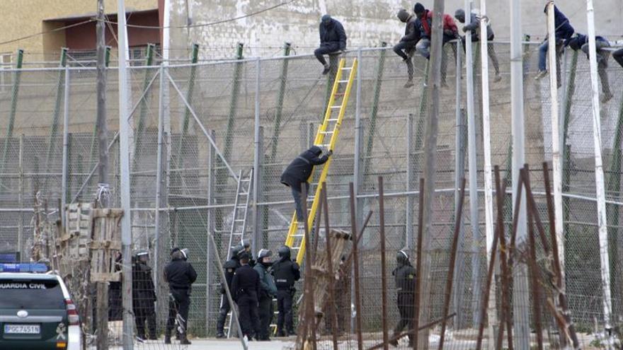 Imagen de archivo de varios inmigrantes encaramados a la valla de Melilla.