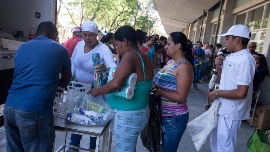 Una mujer compra productos básicos en Caracas mientras otras hacen cola.