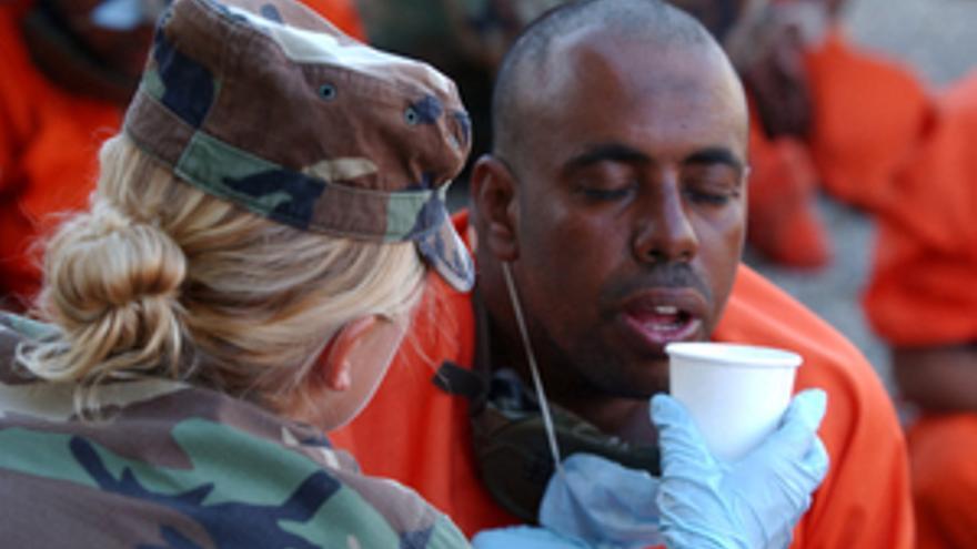 Una militar norteamericana proporciona agua a detenidos a su llegada al Campo X, en Guántanamo. © US DoD