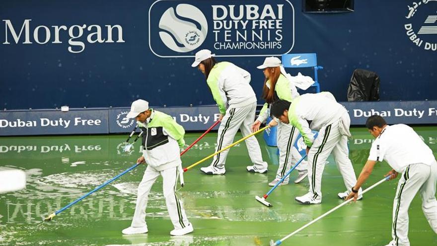 Voluntarios retiran el agua de la pista durante el torneo de Dubái que se celebra en Dubái (Emiratos Árabes Unidos) en el partido suspendido entre Carla Suárez y Caroline Garcia. EFE/Ali Haider