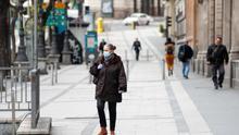 Una mujer con mascarilla pasea por la calle de Alcalá durante el estado de alarma decretado por el Gobierno para combatir el coronavirus, en Madrid (España)