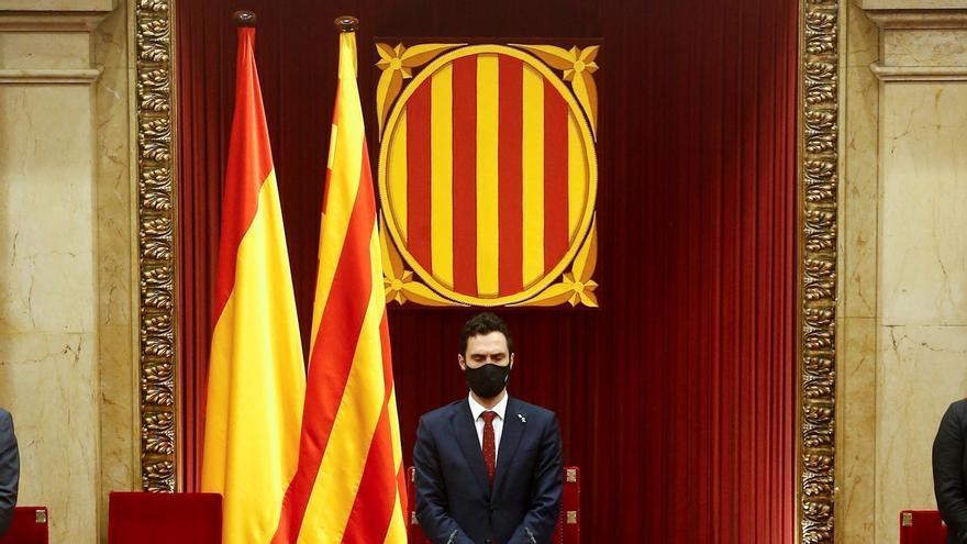 El presidente de la Generalitat, Quim Torra (c) guarda un minuto de silencio en honor a las víctimas del coronavirus junto a los diputados del Parlament de Cataluña al inicio del pleno monográfico sobre la COVID- .
