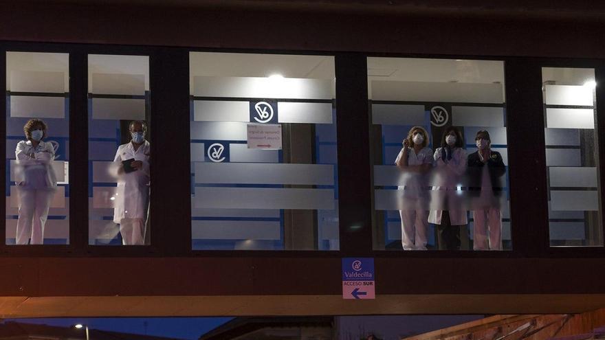Personal sanitario de Valdecilla observando desde los ventanales a la hora de los aplausos | JOAQUÍN GÓMEZ SASTRE