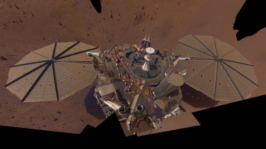 Fotografía reciente del lander o aterrizador InSight sobre la superficie de Marte. En ella se aprecian los dos booms blanquecinos (destacan sobre los paneles solares) que conforman el instrumento