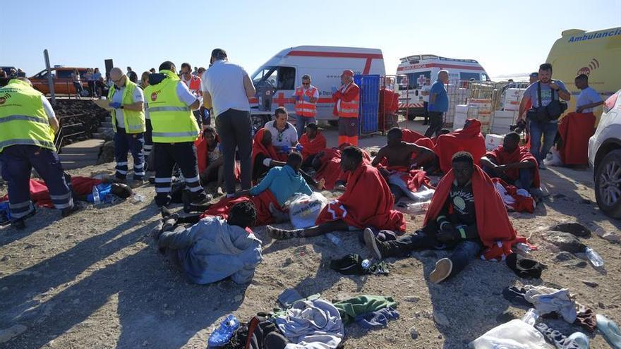 Un grupo de personas en la playa del Burrero son atendidas por servicios de emergencia tras llegar en patera.