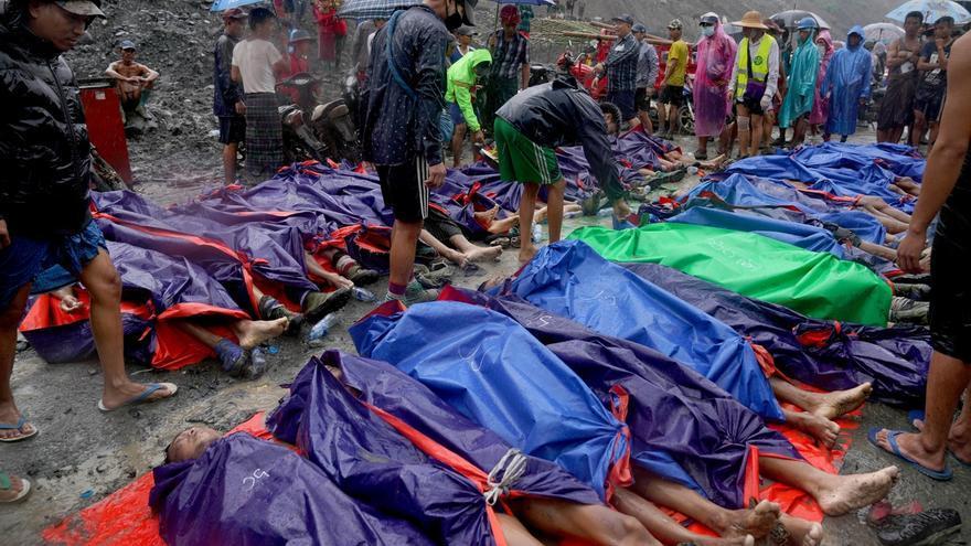 Amigos y familiares junto a las víctimas tras el deslizamiento de tierra en una mina de jade en Hpakant, estado de Kachin, Myanmar. Los esfuerzos de búsqueda y rescate continúan tras el deslizamiento de tierra provocado por fuertes lluvias.