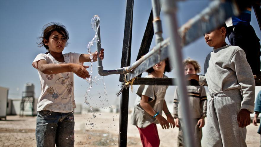 Un grupo de niños recoge agua de un punto de distribución. El campo de Za'atari en Jordania alberga a 125.000 refugiados de los casi dos millones de personas que han huido de la guerra de Siria, en su mayoría mujeres y niños. Jordania/ Pablo Tosco/Oxfam Intermón
