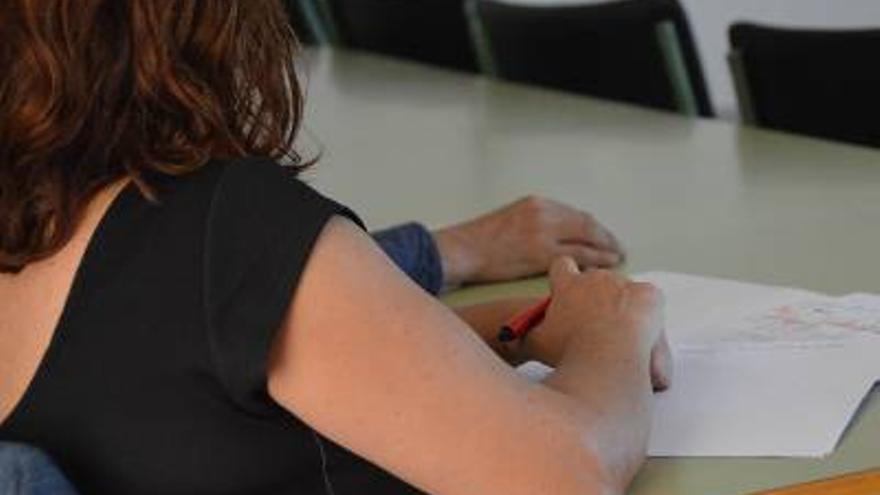 Estudiante toma apuntes durante una clase.