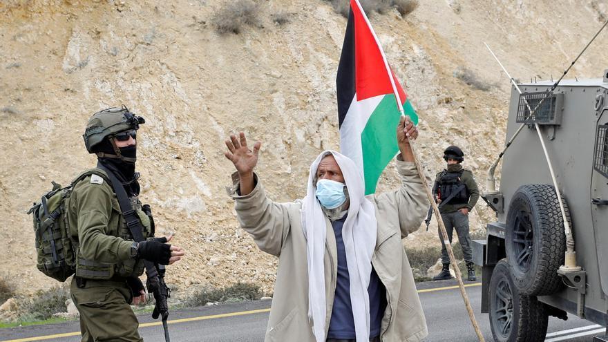 Un manifestante sujeta la bandera palestina en una protesta frente a las fuerzas israelíes en Masafer Yatta, cerca de Hebrón