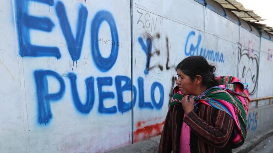 Una mujer camina frente a una pintada en apoyo al presidente Evo Morales en La Paz.