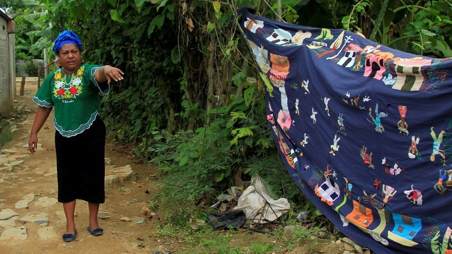 Fotografía del 15 de junio de 2020 que muestra a la defensora de derechos humanos y líder de la Asociación Mujeres Tejiendo Sueños y Sabores de Mampuján, Juana Ruiz, junto a un tapiz que cuenta la historia de la violencia vivida por los habitantes de Mampuján a manos de los paramilitares en el año 2000, en Mampuján (Colombia).