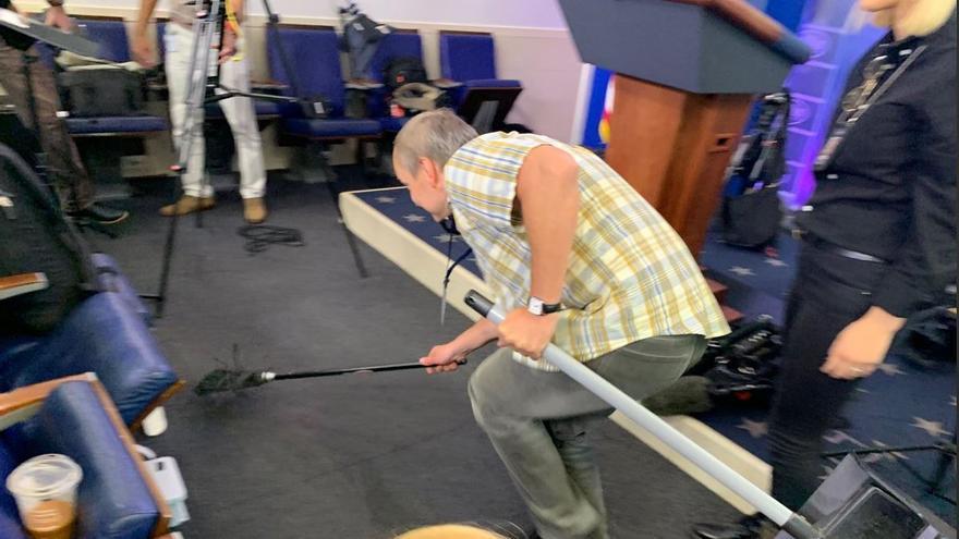 Un informador trata de atrapar a un ratón en la sala de comparecencias de la Casa Blanca