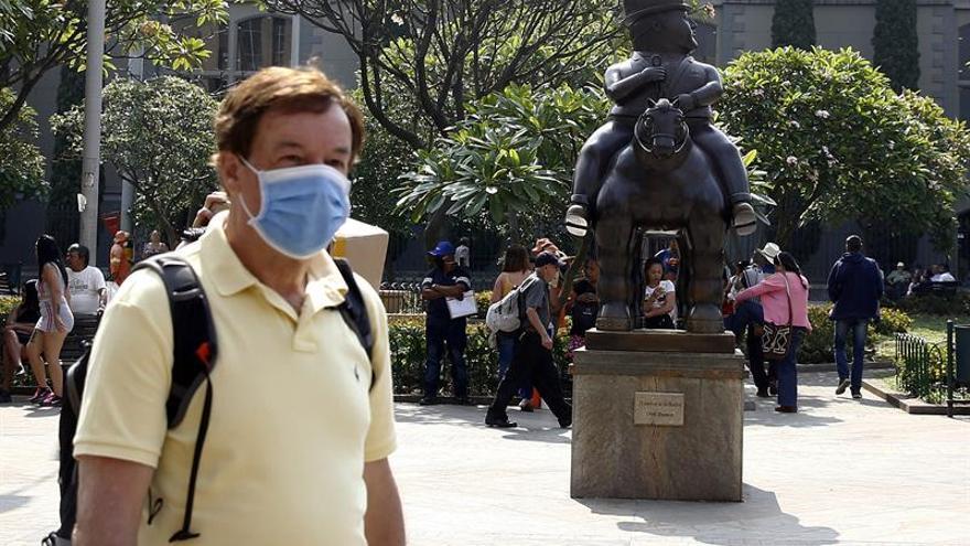 Un hombre con tapabocas camina cerca a una escultura de Fernando Botero como medida contra el coronavirus en Medellín (Colombia).