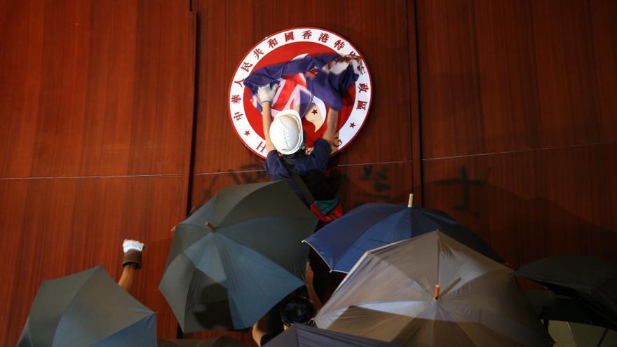 Un manifestante coloca una bandera británica sobre el emblema de Hong Kong tras irrumpir en la sede del Parlamento, este lunes en Hong Kong