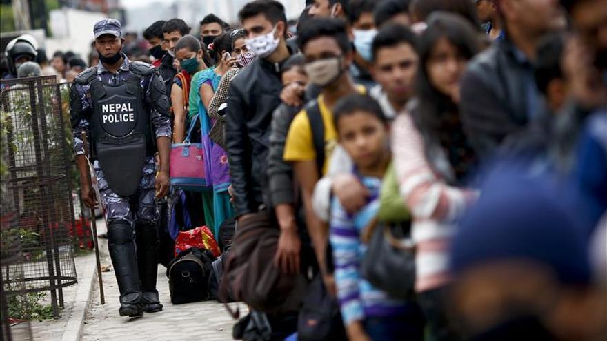 Un agente de la policía nepalí camina junto a una cola de gente que espera coger un autobús fletado por el gobierno para regresar a sus hogares a las afueras de Katmandú (Nepal). EFE