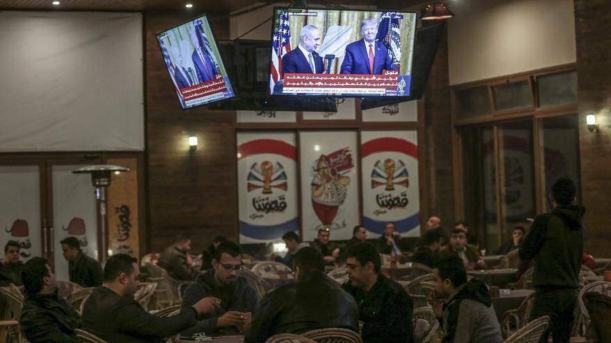 Palestinos en una cafetería en Gaza, mientras retransmiten en la televisión la presentación del presidente estadounidense Donald Trump y el primer ministro israelí Benjamin Netanyahu del acuerdo de paz