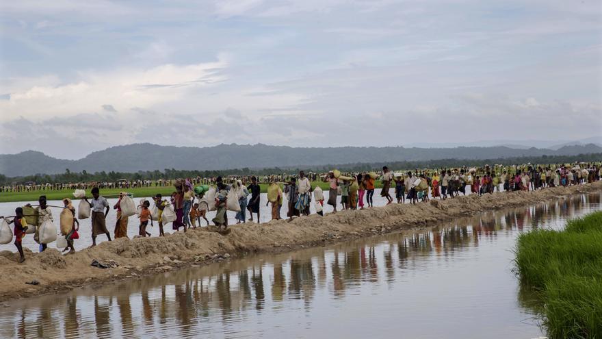 Musulmanes rohingya, que pasaron cuatro días al aire libre después de cruzar desde Myanmar a Bangladesh, llevan a sus hijos y sus pertenencias después de que se les permitiera avanzar hacia un campo de refugiados, en Palong Khali, Bangladesh, el 19 de octubre de 2017. Foto: AP / Dar Yasin.