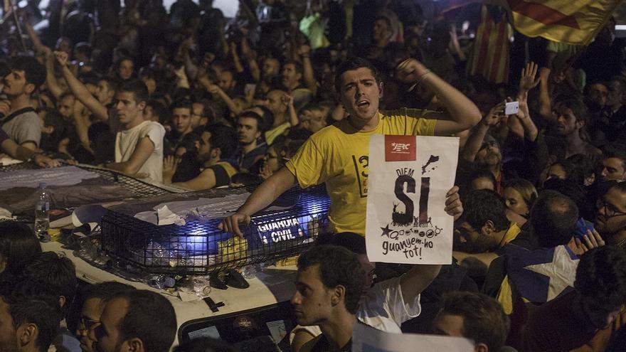 Protestas en el exterior de la Conselleria de Economia de la Generalitat, con manifestantes apoyados en un coche de la Guardia Civil.
