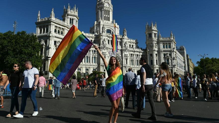 Una joven celebra la diversidad sexual cubierta por la bandera LGTBI