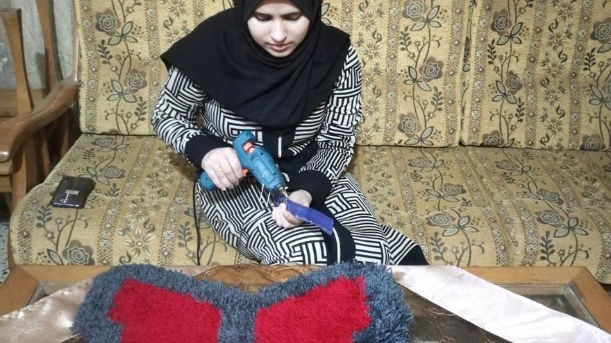 Maram confeccionando una de sus alfombras