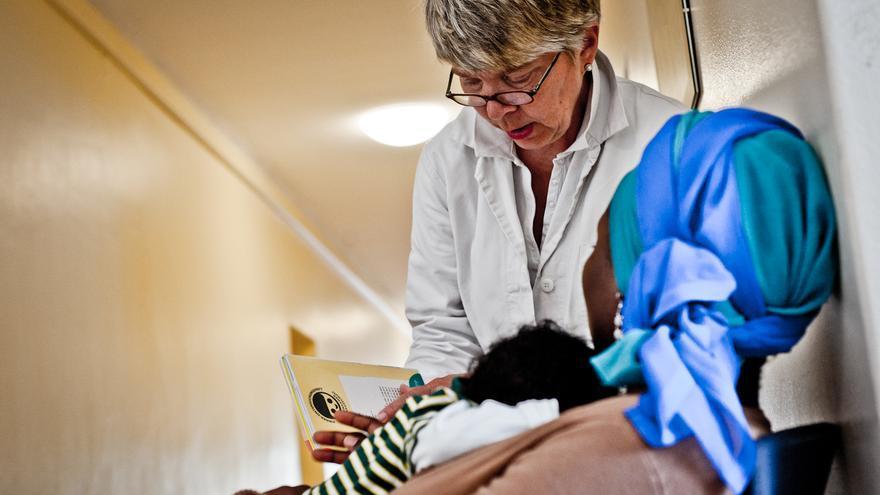 Una de las doctoras voluntarias revisa la cartilla infantil de una paciente de ghanesa que carece de seguro médico
