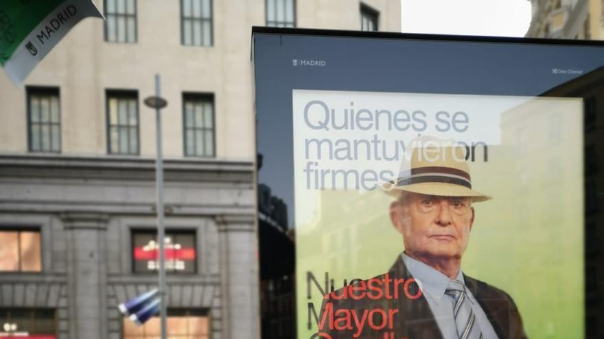 """Juan Pablo y su pareja frente al cartel de la campaña """"Nuestro Mayor Orgullo"""" que protagoniza."""