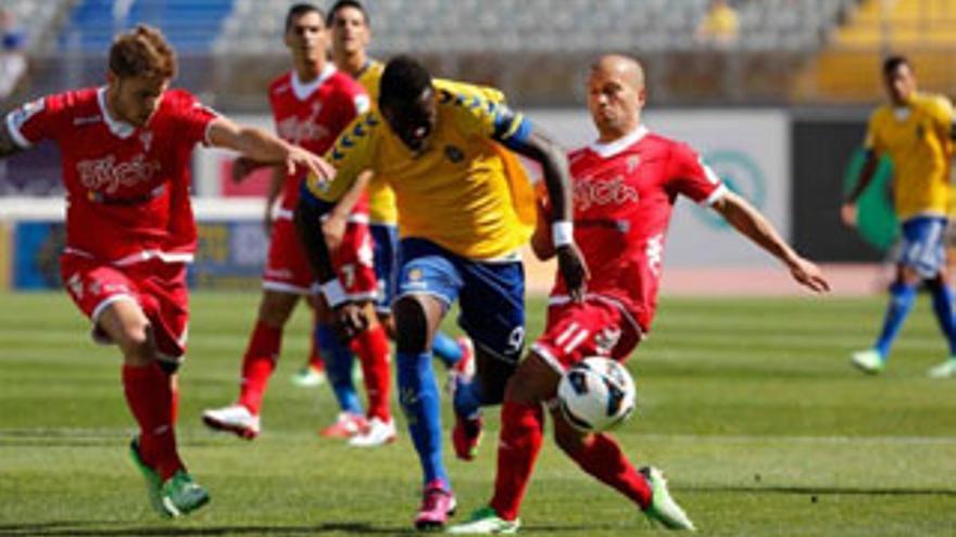 El delantero Macauley Chrisantus deja atrás a dos defensas durante el partido que la UD Las Palmas disputó ante el Sporting de Gijón. udlaspalmas.es